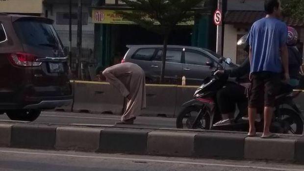 Pria salat di tengah jalan.
