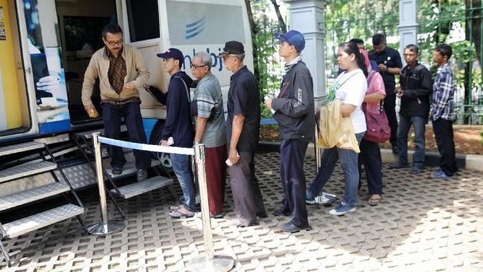 Warga berbondong-bondong untuk menukarkan uang rceh di Lapangan IRTI Monas, Jakarta, Selasa (22/5/2018). Mereka rela antre panjang dan berpanas-panasan demi untuk menukarkan uang receh.