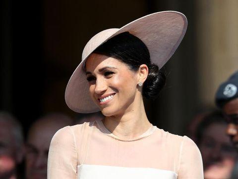 Meghan Markle melengkapi gayanya dengan topi Philip Treacy.