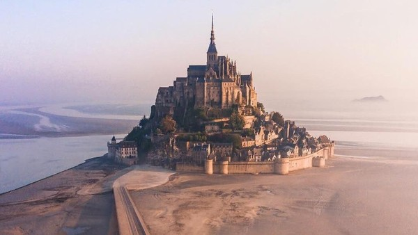 Sejarahnya, Mont Saint Michel merupakan bangunan monastik pertama pada abad ke-8. Pulau karang yang menjadi pijakan biara yang berbentuk kastil ini bernama Mont Tombe (nomadlad/Instagram)