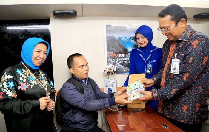 Deputi Gubernur Bank Indonesia Rosemaya Hadi menyaksikan Direktur Jaringan dan Layanan Bank BRI Osbal Saragi Rumahorbo melayani penukaran uang Hasil Cetakan Sempurna (HSC) pecahan kecil kepada nasabah Bank BRI di layanan keliling E-Buz Bank BRI yang dilakukan di Monumen Nasional (Monas) Jakarta, Rabu (23/5). Foto: dok. BRI