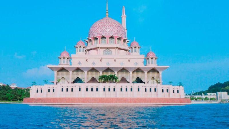 Masjid Putra di Putrajaya, Malaysia memiliki warna dan arsitektur menarik. Masjidnya berwarna pink dengan kubah berkaligrafi yang indah. Warna masjid ini dari granit berwarna pink. (numacho22/Instagram)