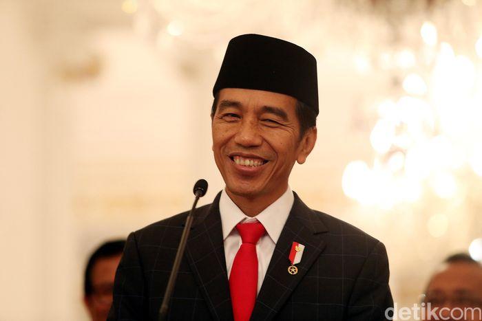 Jokowi tersenyum di sela-sela mengumumkan THR dan gaji ke-13 bagi PNS dan pensiunan.