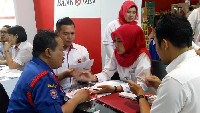 Karyawan Bank DKI tengah menjelaskan aplikasi JakOne Mobile kepada pengunjung Pekan Raya Jakarta di Jakarta (23/5/2018).