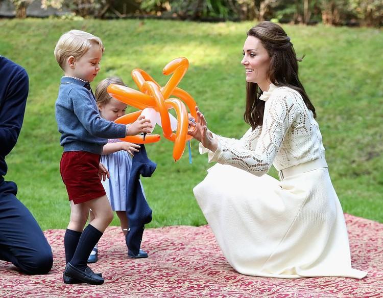 Pangeran George asyik bermain balon bersama ibunya, Kate Middleton. Aih, senang ya, George? Sementara itu Putri Charlotte sibuk dengan cardigannya, hi-hi. (Foto: Getty Images)