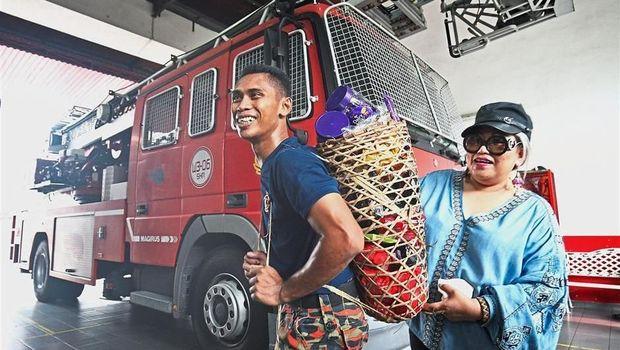 Warga Malaysia memberi cokelat ke pemadam kebakaran /