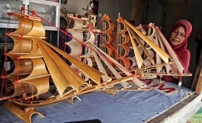 Seorang pengrajin memperlihatkan kerajinan bambu berupa kapal pinisi di Marunda, Jakarta Utara, Rabu (30/5/2018).