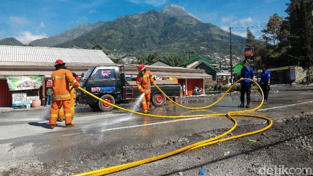 Tim pemadam kebakaran menyiram abu yang menyelimuti jalanan di Kecamatan Selo, Boyolali.