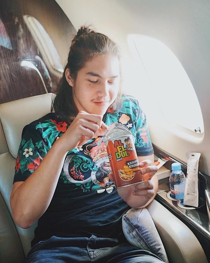 Anak kedua pasangan Ahmad Dhani dan Maia Estianty ini sedang di pesawat pribadi. Ia memilih ngemil keripik singkong produksinya bersama sang kakak Al dan adiknya, Dul. Foto: Instagram elrumi