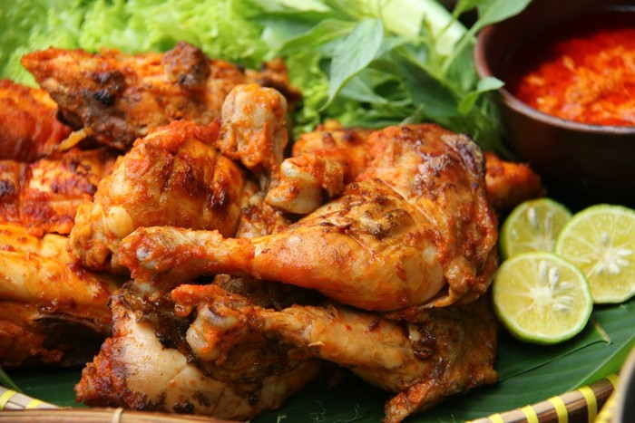 Close-up view of chicken pieces marinated in rich Javanese spices then grilled over charcoal fire. The chicken is arranged on a banana-leaf-lined bamboo tray.