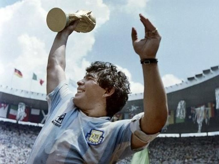 Argentinas soccer star team captain Diego Maradona brandishes the World Soccer Cup won by his team after a 3-2 victory over West Germany on June 29, 1986 at the Azteca stadium in Mexico City. / AFP PHOTO / STAFF