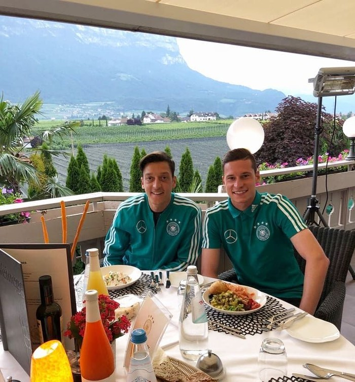 Bersama dengan teman satu timnya, Ozil terlihat tengah asyik menikmati makan di sore hari. Pemandangan yang ada di belakang Ozil pun bikin gagal fokus. Foto: Instagram @m10_official