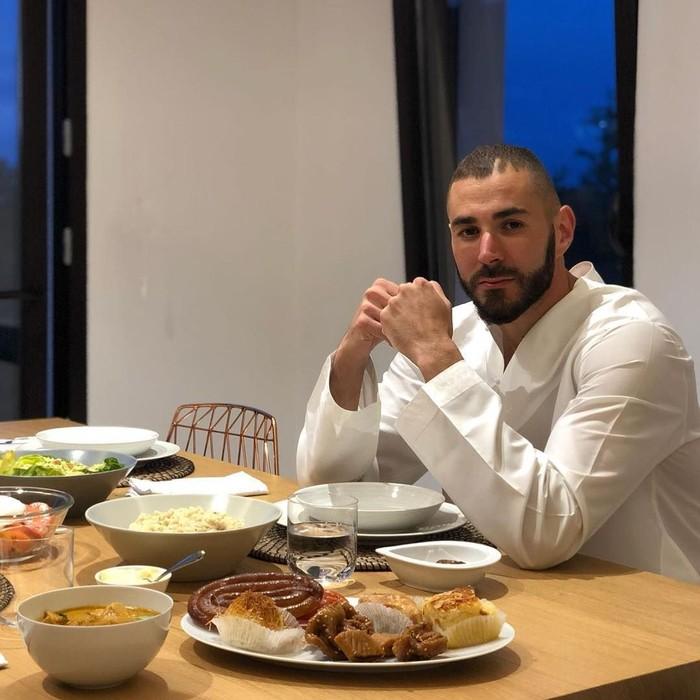 Pemilik nama lengkap Karim Mostafa Benzema ternyata suka makan. Lihat saja nih di hadapannya berjejer makanan hingga dessert yang siap disantap. Foto: Instagram @karimbenzema