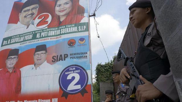 Aparat bersenjata berjaga saat KPK menggeledag rumah Syahri Mulyo, di Ngantru, Tulungagung, Jawa Timur, Sabtu (9/6).
