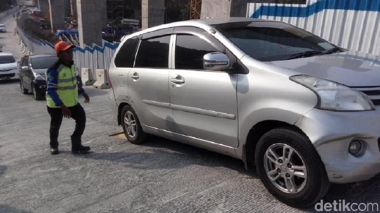 Petugas mengganjal mobil yang tidak kuat di tanjakan Jembatan Kali Kenteng, Susukan, Kabupaten Semarang Foto: Eko Susanto/detikcom