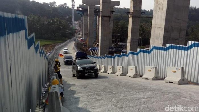 Petugas ganjal mobil yang tidak kuat di tanjakan Jembatan Kali Kenteng, Susukan, Kabupaten Semarang, Minggu (10/6/2018).