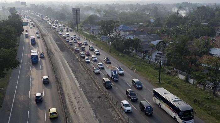 Foto aerial kepadatan kendaraan di ruas Tol Jakarta-Cikampek KM 38, Cikarang, Bekasi, Jawa Barat, Sabtu  (9/6). Kemacetan terjadi karena adanya peningkatan volume kendaraan saat arus mudik Lebaran 2018 serta adanya penyempitan jalan dan para pemudik yang ingin masuk ke rest area KM 39. ANTARA FOTO/Hafidz Mubarak A/pras/18