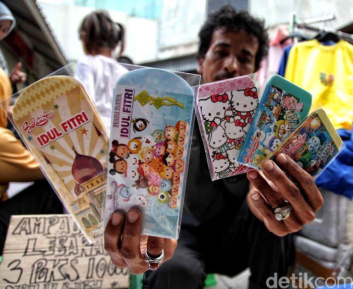 Seorang pedagang memamerkan aneka amplop yang dijualnya di depan kamera.