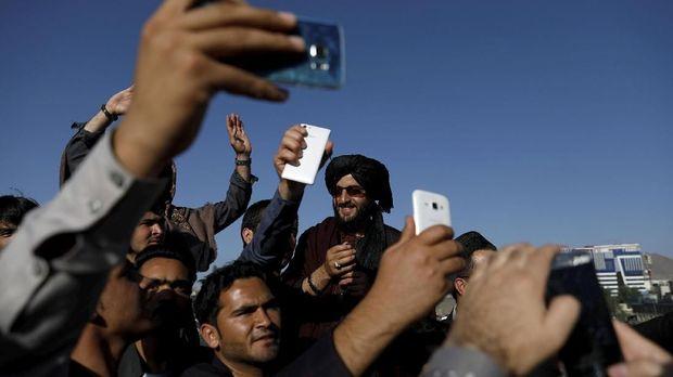 Warga berswafoto dengan Taliban saat gencatan senjata Idulfitri, di Afghanistan, Juni.