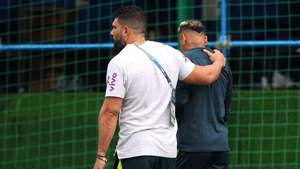 Neymar (kanan) didampingi ofisial timnas Brasil saat meninggalkan lapangan latihan.