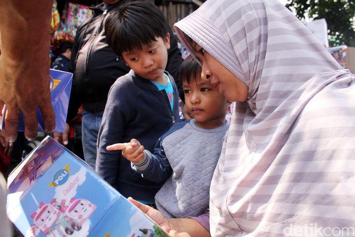 Para orang tua menemani anaknya membeli mainan di Pasar Gembrong.