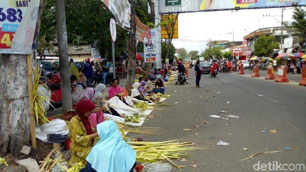 Para pedagang janur dan selongsong ketupat berjualan di pinggir jalan