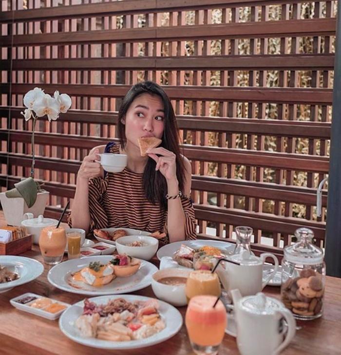 Gigit roti dan pegang cangkir kopi, ini sarapan terakhir Gani sebelum plesiran ke Vietnam. Sarapannya lengkap banget ya? Foto: Instagram ganegani