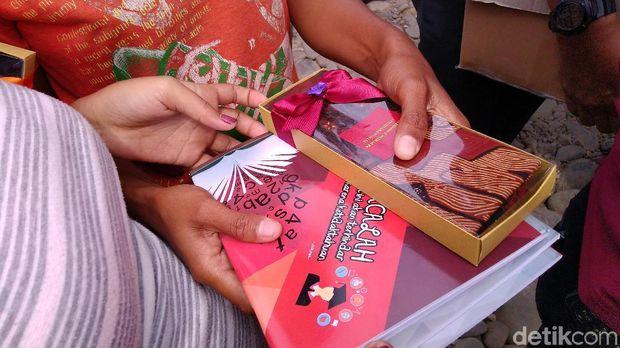 Selain kain batik, Jokowi juga membagikan buku kepada warga