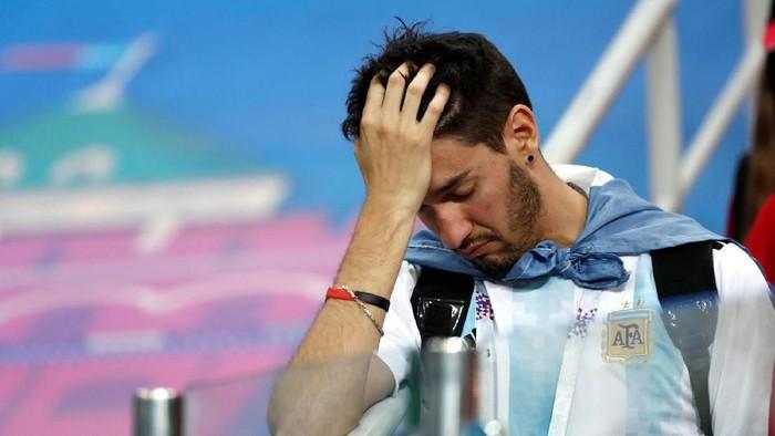 Ekspresi kesedihan salah satu penggemar timnas Argentina ketika menyaksikan mereka kalah telak. Foto: Reuters
