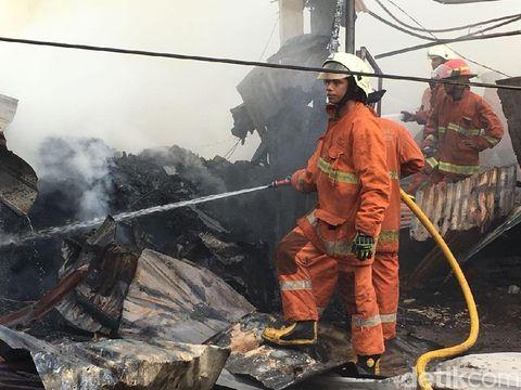 Asap di lokasi masih pekat, petugas masih menyemprot air untuk memastikan api benar-benar mati