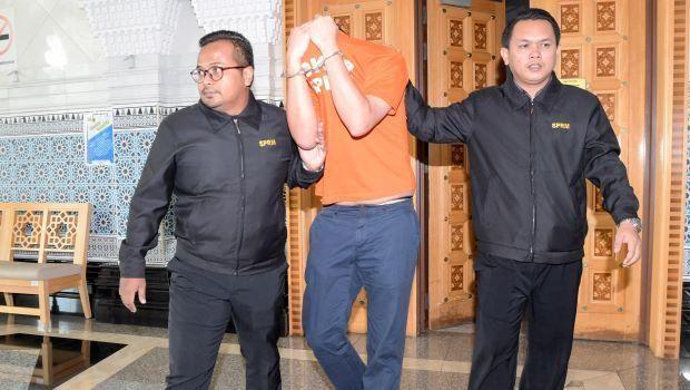 Mantan staf Najib menutup wajahnya saat dibawa ke pengadilan pada Senin (25/6) pagi