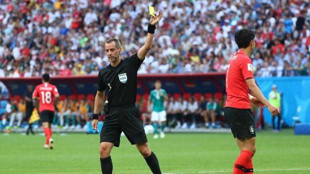 Wasit Mark Geiger memberikan kartu kuning kepada pemain timnas Korea Selatan Son Heung-min.