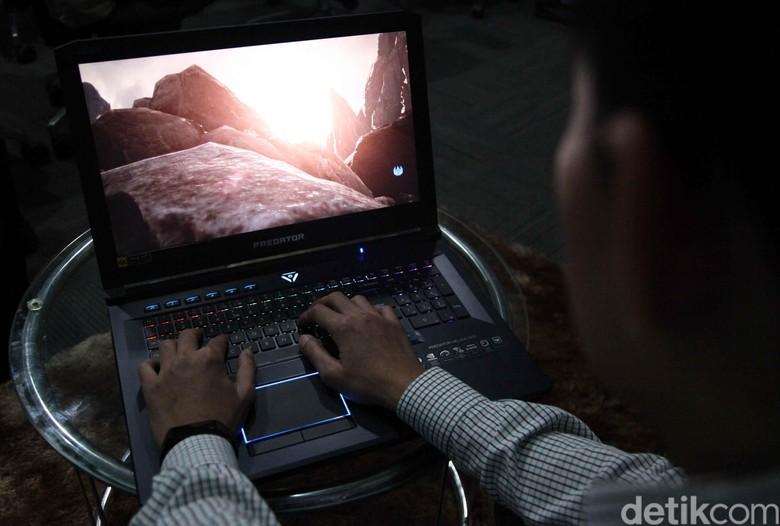 Seorang pekerja mengoperasikan laptop gaming terbaru Acer.