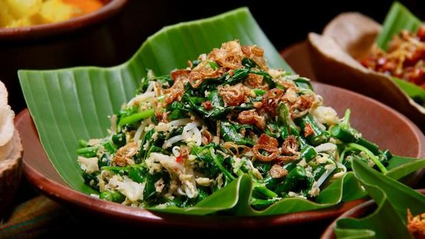 Jukut Urap, the popular Balinese vegetable salad accompanying many Balinese meals, especially Nasi Campur Bali. Cooked spinach, long beans and bean sprouts mixed with spicy grated coconut. Served on an earthenware plate lined with banana leaf.