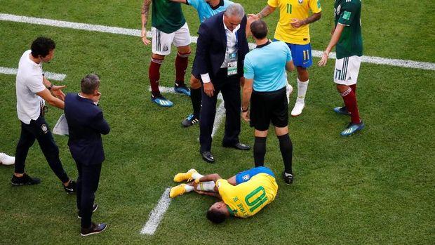 Neymar tergelatak sambil mengerang kesakitan usai terinjak pemain timnas Meksiko Miguel Layun, dalam laga di Samara Arena, Samara, Rusia, 2 Juli. 2