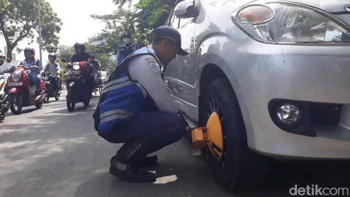 Petugas dishub menggembok roda mobil yang parkir sembarangan (Foto: Zaenal Effendi)