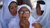 Seorang ibu tampak memanjatkan doa untuk keluarganya yang jadi korban.