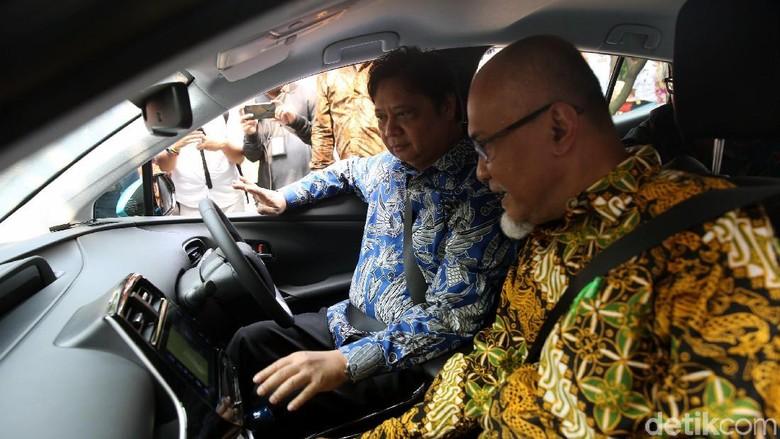 Menperin Airlangga Hartarto dan Presdir Toyota Motor Manufacturing Indonesia Warih Andang Tjahjono mencoba mobil listrik Toyota Foto: Agung Pambudhy