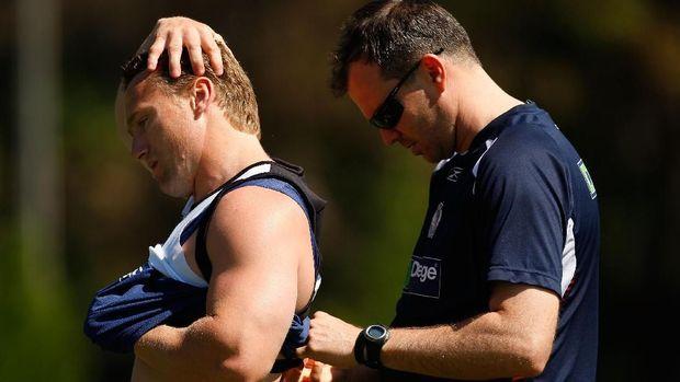 Pelatih sedang membantu pemain memasang 'smart vest' yang berfungsi sebagai fitness tracker.