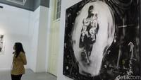 Pengunjung berdiri di depan lukisan di atas kanvas yang terbuat dari arang. Foto: Tia Agnes/ detikHOT