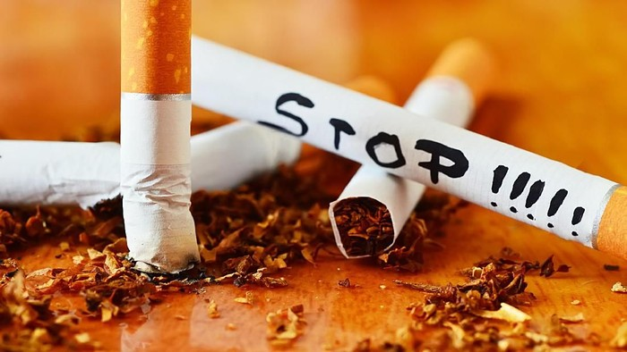 cigarette, tobacco and stop message isolated on wood background close up shot
