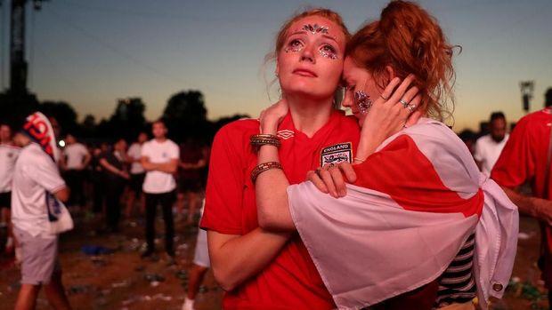 Fan Inggris bersedih seusai kekalahan tim kesayangannya di Piala Dunia 2018, di Hyde Park, London.