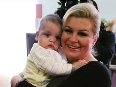 Melempar senyum manis saat berpose bersama seorang bayi. (Foto: Instagram @kolinda_grabar_kitarovic)