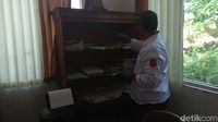 Polisi geledah salah satu ruang di kantor Desa Sekarwangi Karawang.