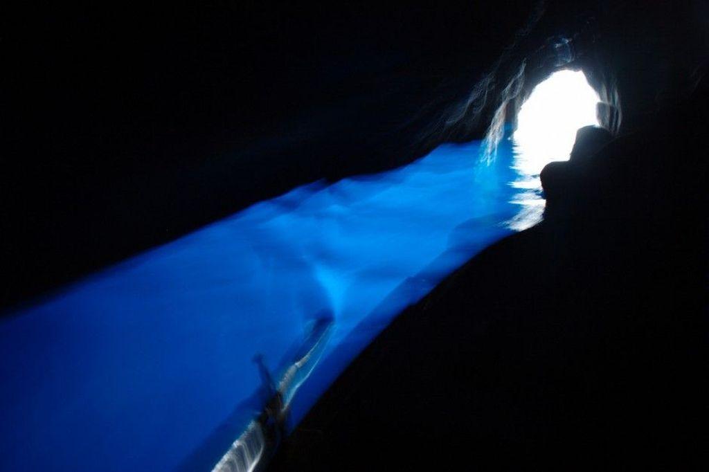 Blue Grotto di Capri, Italia, sangat dekat dengan permukaan air laut sehingga pengunjung kerap menggunakan perahu motor, lalu berganti menggunakan sampan, kemudian berenang agar bisa masuk ke dalam gua. Foto: Matador Network