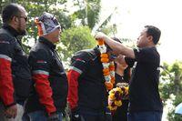 Direktur Sales PT Yamaha Indonesia Motor Manufacturing (YIMM) Sutarya mengalungkan bunga kepada rider MAXI Tour de Indonesia (Foto: dok. Yamaha)