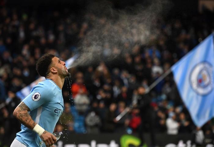 Pemain Manchester City Kyle Walker memuntahkan kembali minumannya saat tanding melawan West Bromwich Albion. Teknik ini dipercaya bisa merangsang otak terhadap karbohidrat. (Foto: Getty Images)
