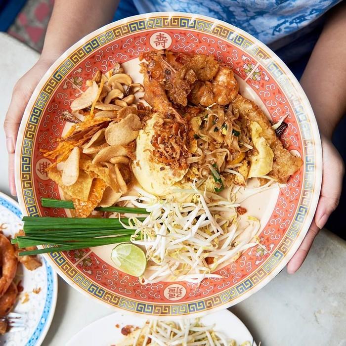 Wongnai punya dua host baru yang bertugas mengulas makanan. Aksi mereka jadi viral lantaran ekspresinya sangat lurus saat mencicip makanan enak. Untuk pad thai, keduanya merekomendasikan pad thai udang buatan Pad Thai Narok Taek di Lat Ya Road. Foto: Wongnai