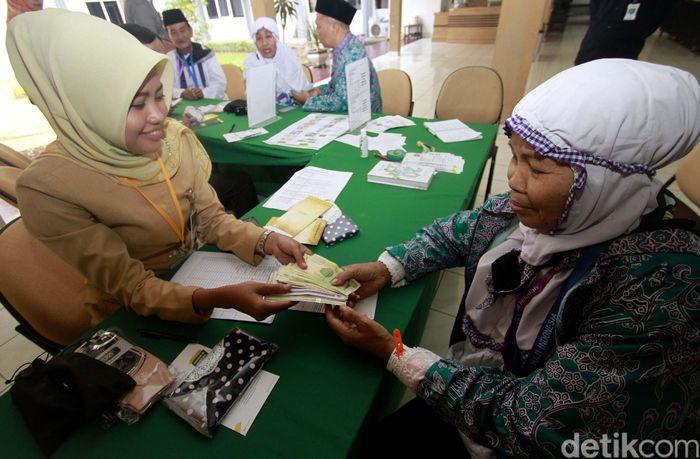 Pegawai PT Bank Syariah Mandiri (Mandiri Syariah) tengah melayani jemaah haji Indonesia yang sedang menukar Saudi Arabian Riyal (SAR) di Embarkasi Haji Pondok Gede Jakarta, Selasa, (17/7/2018).