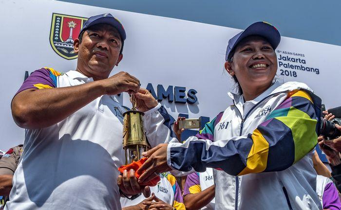 Wali Kota Semarang Hendrar Prihadi (kiri) menerima api obor Asian Games 2018 dari mantan atlet tenis Indonesia, Yayuk Basuki (kanan) saat arak-arakan estafet api obor tersebut di Semarang, Jawa Tengah, Rabu (18/7/2018). Antara Foto/Aji Styawan.